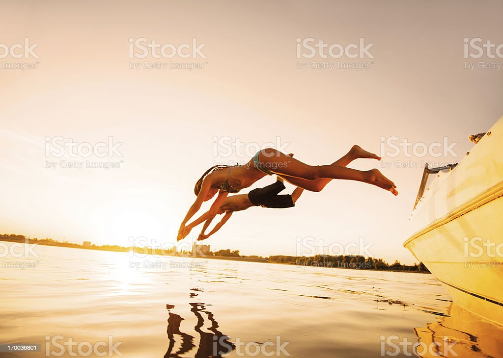 Two people jumping in water against the sunlight. stock photo