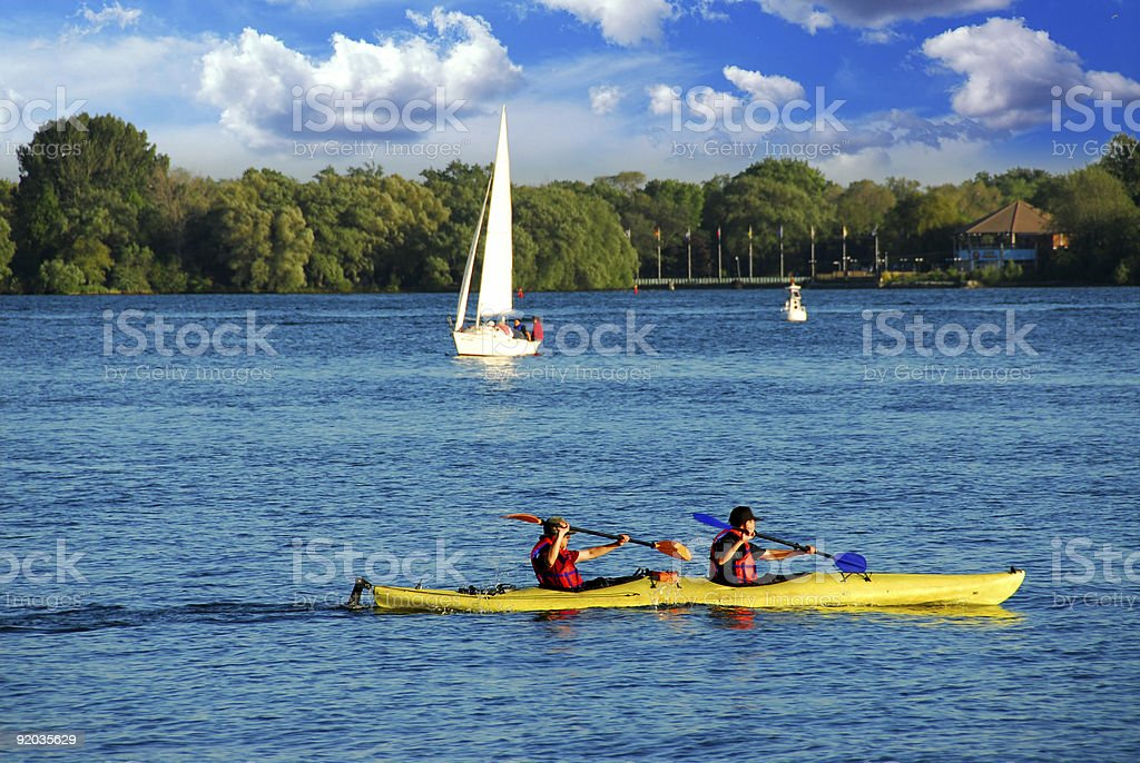 Two people kayak on a lake near a sailboat royalty-free stock photo