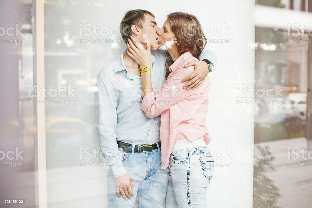 Two people kissing, view through the window stock photo