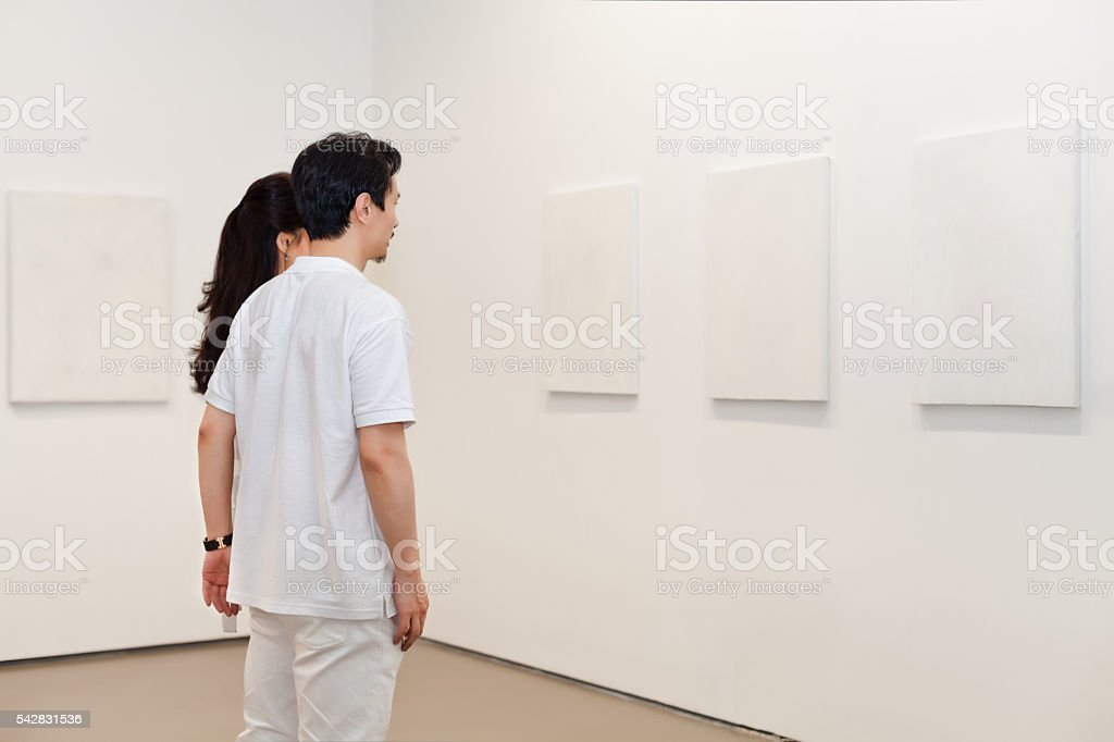 Man and woman looking at white frames in an art gallery