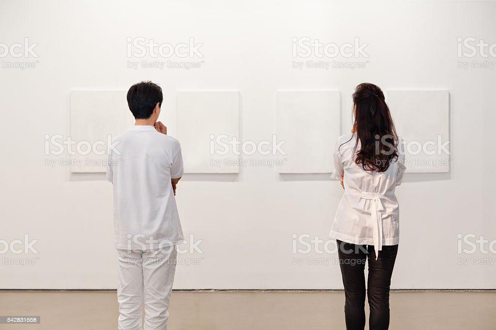 Two people looking at white frames in an art gallery stock photo