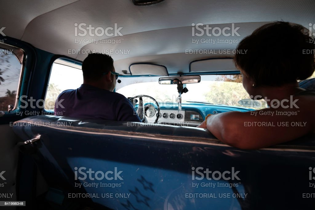 Two people looking forward from the inside of a classic car in Cuba stock photo