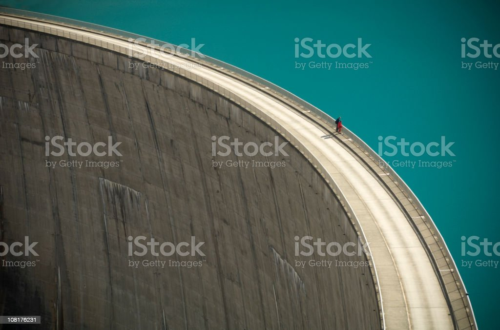 Two People Looking Over the Edge of a Large Dam stock photo