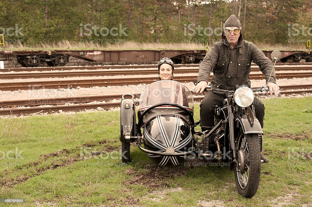 Two people on a 1935 style motorcycle with sidecar stock photo