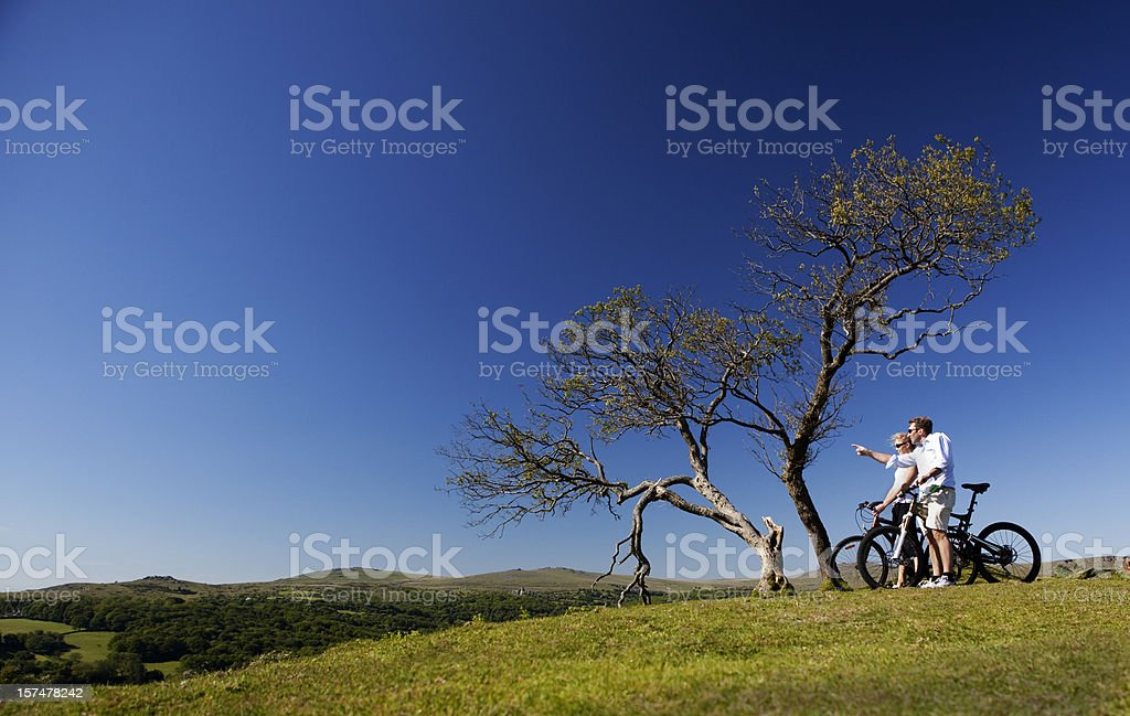 Two people on bikes looking into the distance stock photo