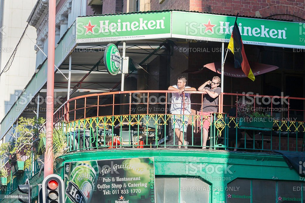 Two people on the balcony at Guildhall pub in Johannesburg stock photo