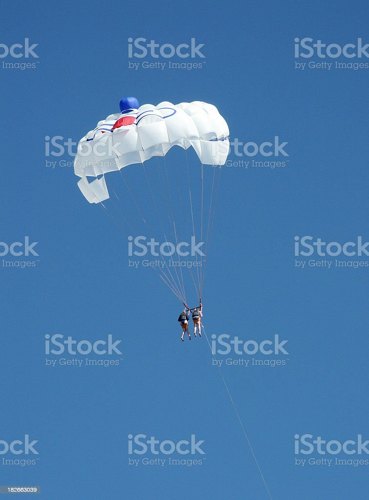Two people parasailing hanging on one sail royalty-free stock photo