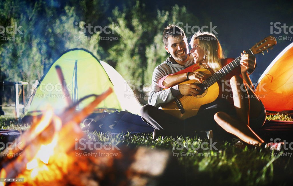 Two people playing guitar by campfire. stock photo