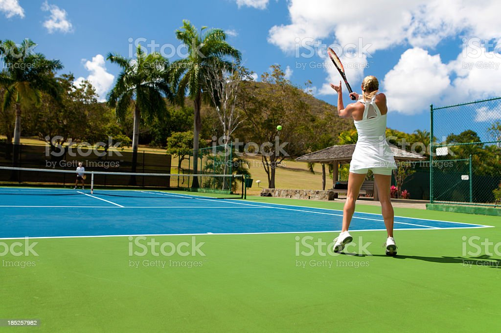two people playing tennis in a tropical setting royalty-free stock photo