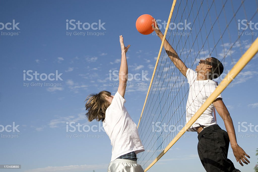 Two people playing volleyball on a sunny day royalty-free stock photo