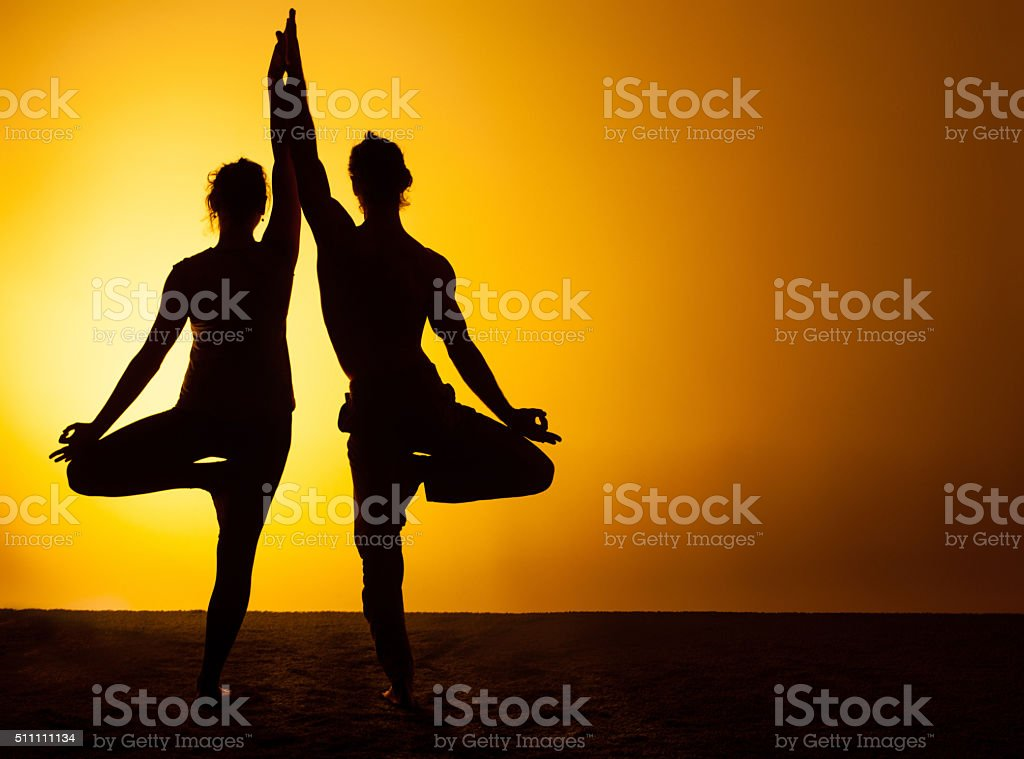 Two people practicing yoga in the sunset light stock photo