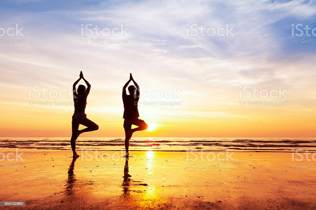 Two people practicing yoga tree position on the beach, sunset stock photo