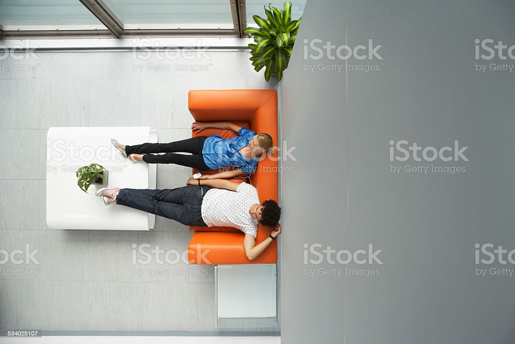 Two People Reclining On Orange Sofa At Office stock photo