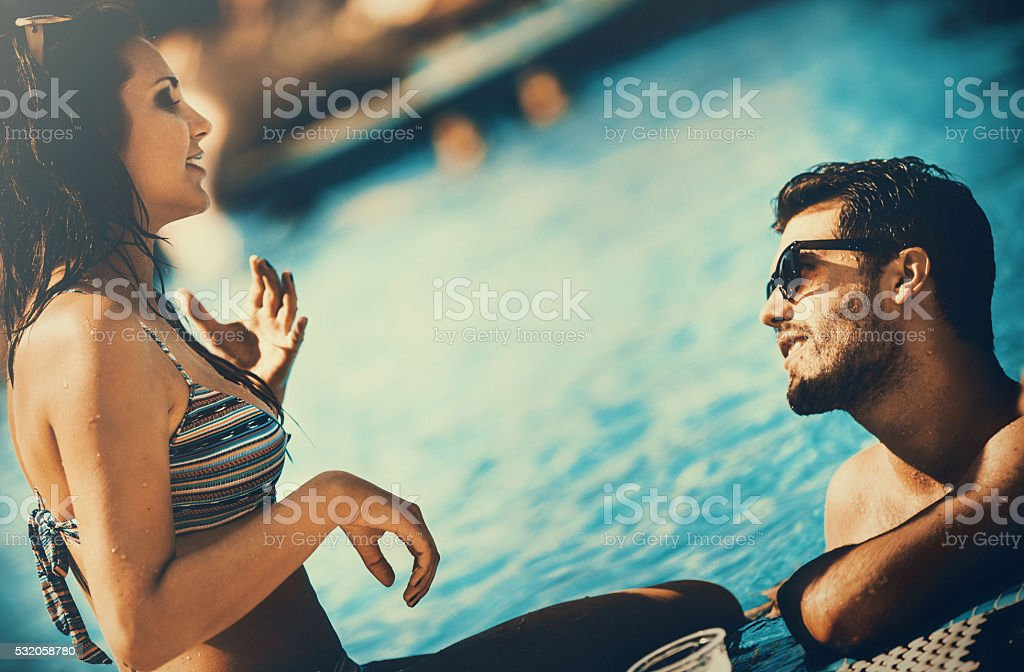 Two people relaxing by swimming pool. stock photo
