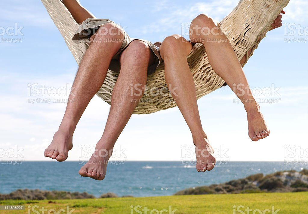 Two people relaxing in a swinging hammock. royalty-free stock photo