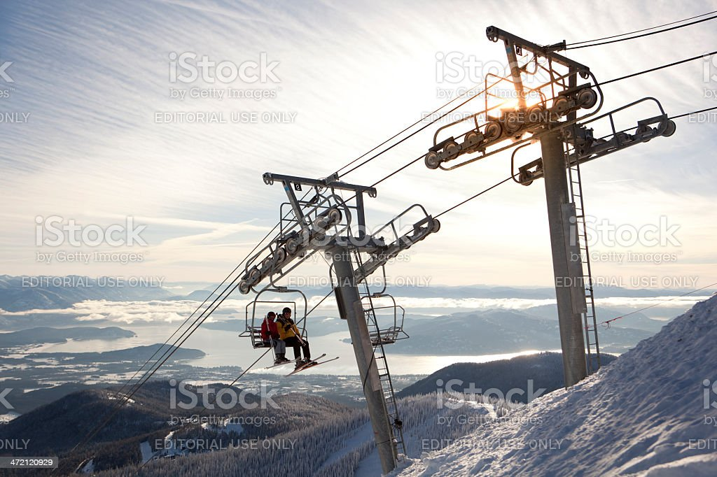 Two people riding a chairlift at Scweitzer Mountain Resort stock photo
