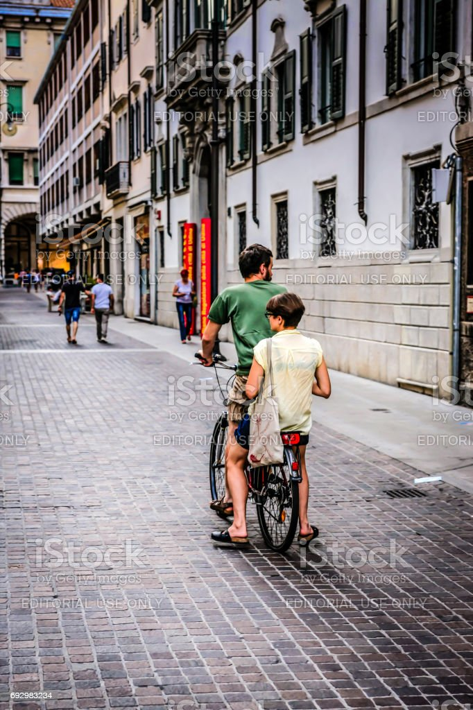 Two people riding a single bicycle in Udine Italy stock photo
