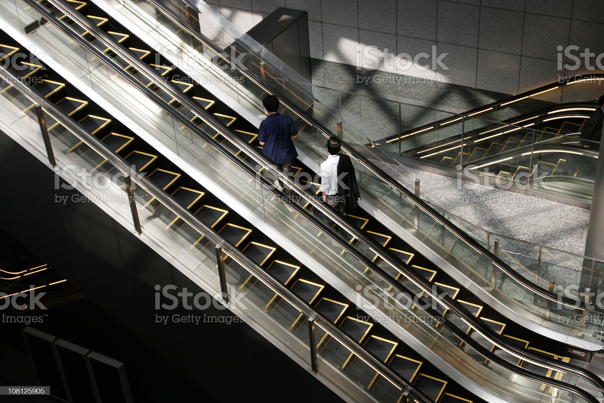 Two People Riding Escalator in Building royalty-free stock photo