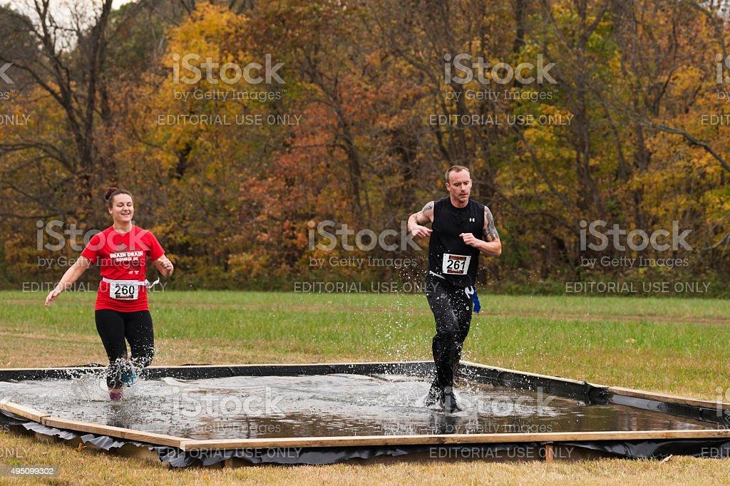 Two people run through water during 5K stock photo