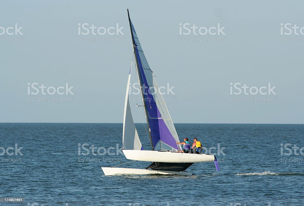 Two people sailing a catamaran in open water stock photo