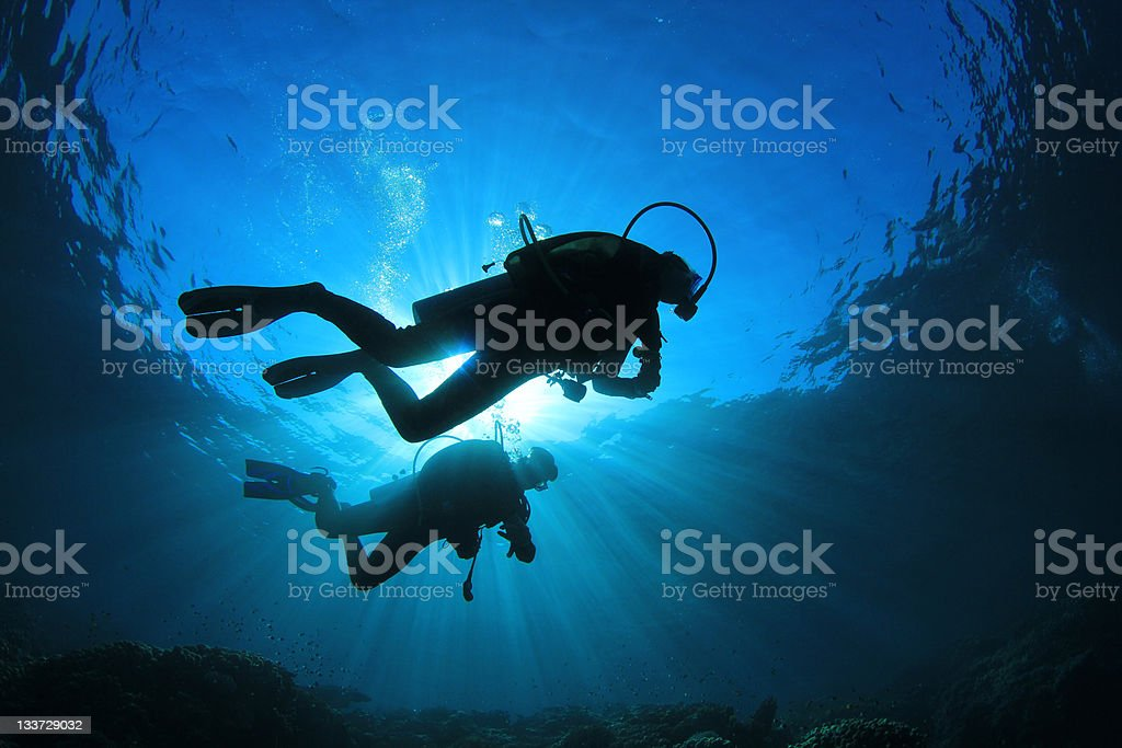 Two people scuba diving with sunlight from above stock photo