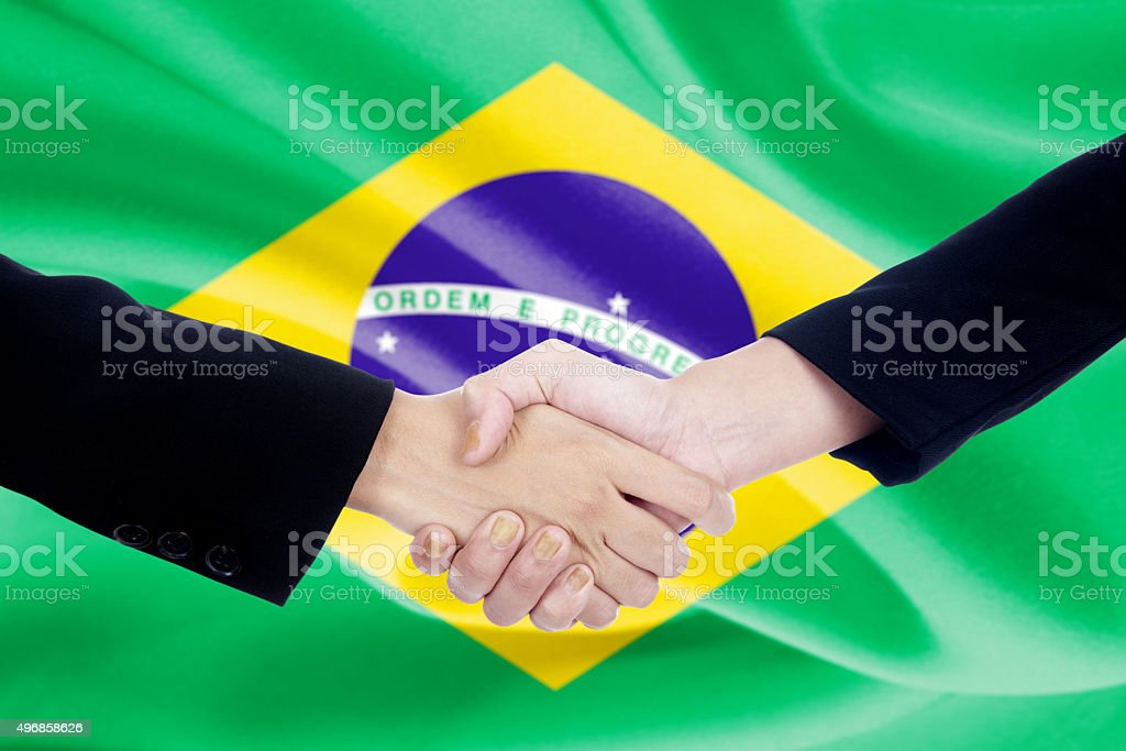 Two people shaking hands with Brazil flag backdrop stock photo