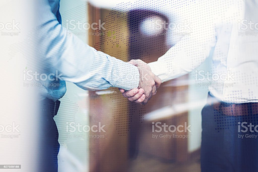 Two people shaking hands with world map behind. royalty-free stock photo