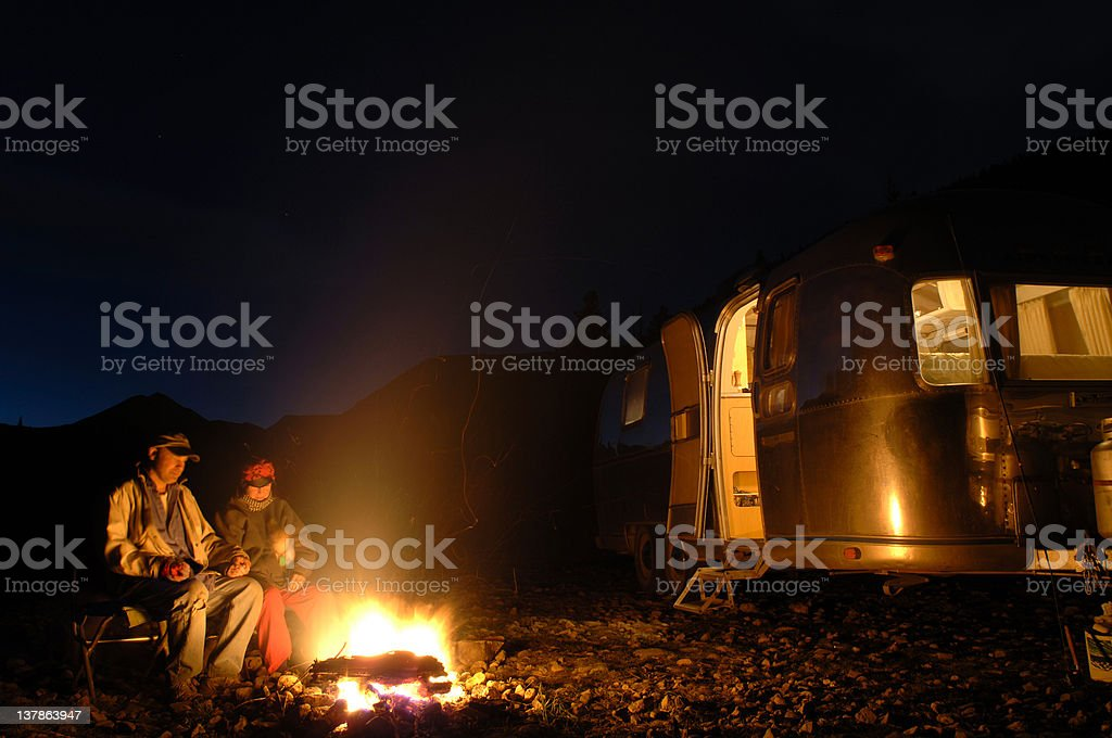Two people sitting by fire at a camp at night stock photo