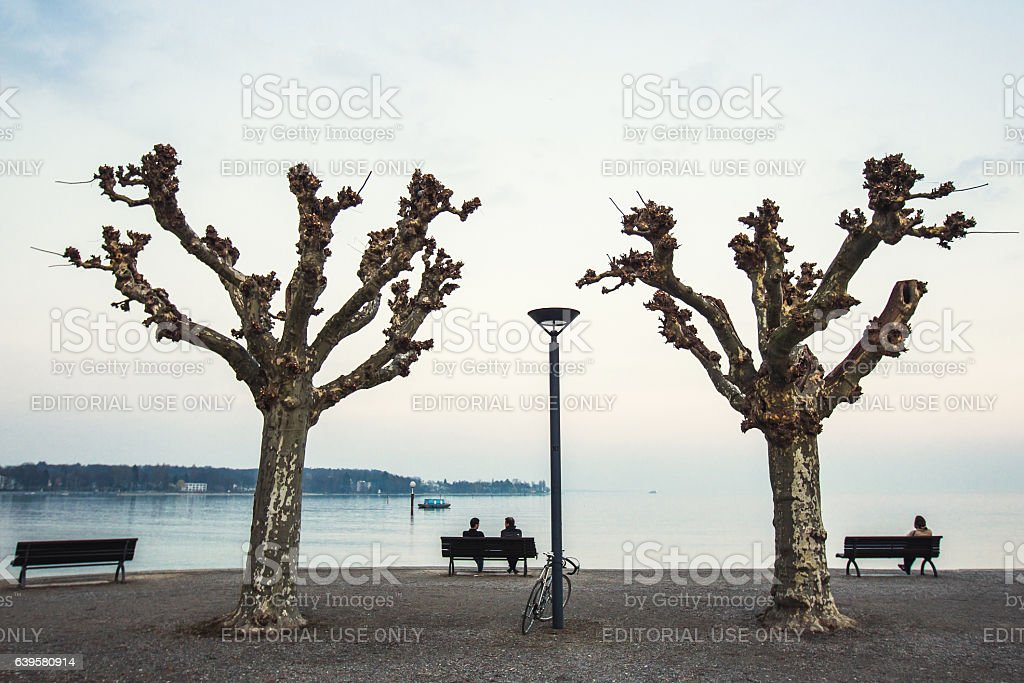 Two people sitting on the waterfront Bodensee lake in morning stock photo