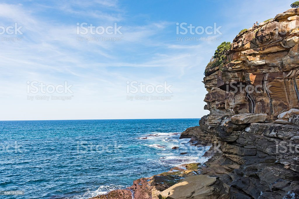 Two people sitting on top of a cliff in Australia stock photo
