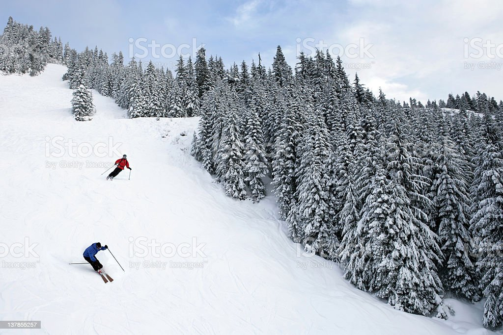 XL two people skiing on steep trail stock photo
