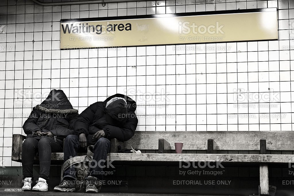 Two People Sleeping in NYC Subway Waiting Area stock photo