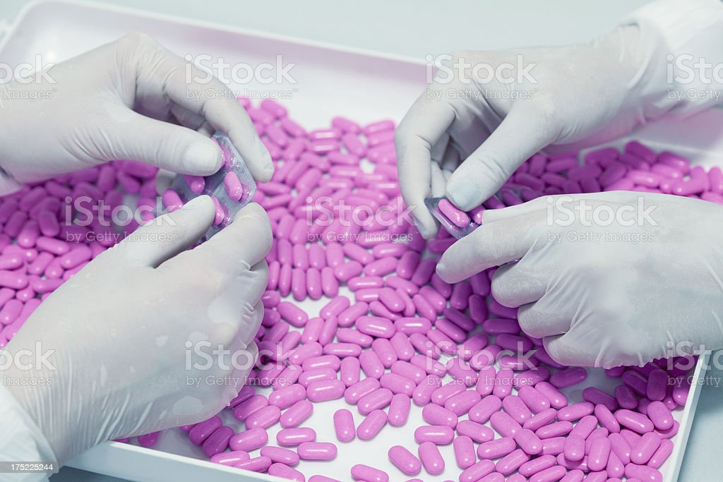 Two people sorting pink pills in a white tray stock photo