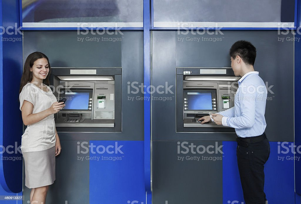 Two people standing and withdrawing money from an ATM stock photo