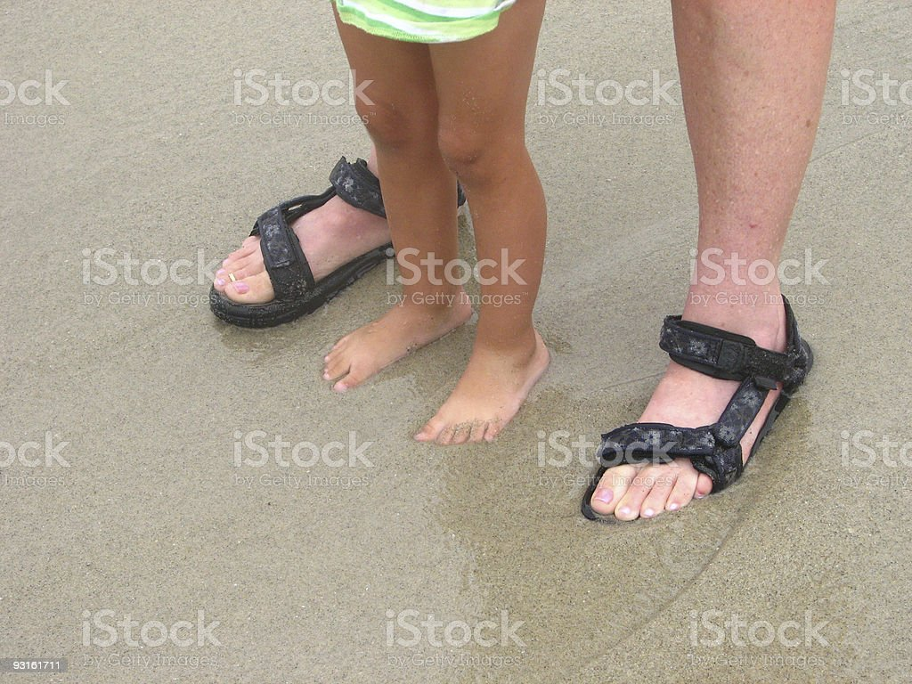 Two People Standing in Wet Sand royalty-free stock photo