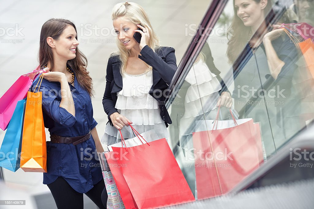 two people standing on escalator, carrying shopping bags royalty-free stock photo