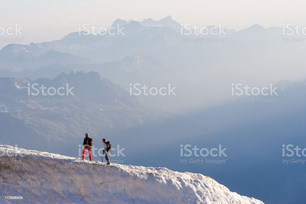 Two people standing on top of an icy mountain top stock photo