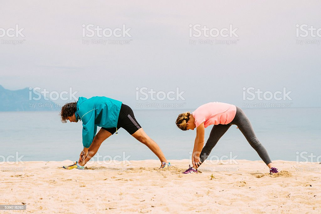 Two people stretching on the sea shore in summer stock photo