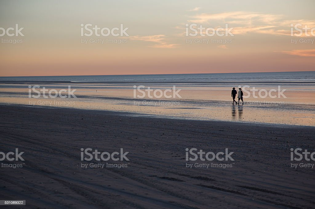 Two people walking along beach at sunset stock photo