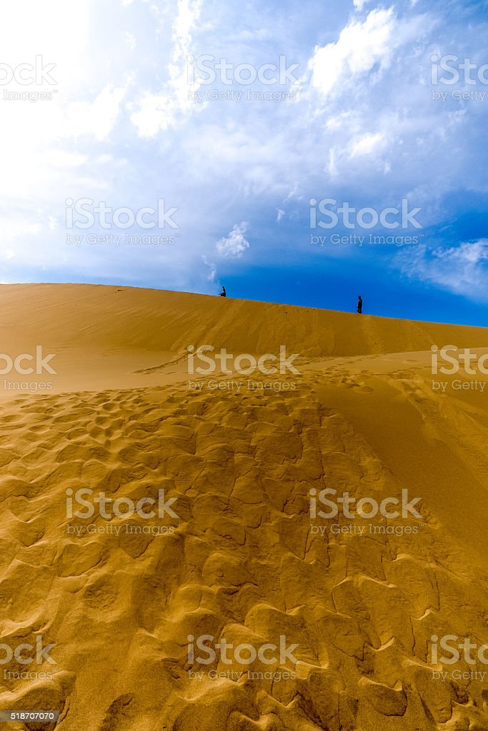 two people walking along the top of dune stock photo