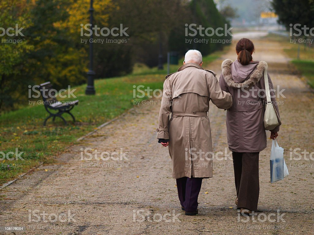 Two People Walking in a Park on Autumn Day royalty-free stock photo