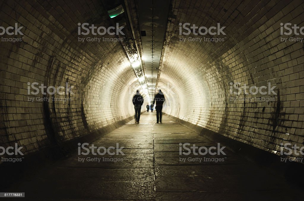 Two people walking in the tunnel stock photo