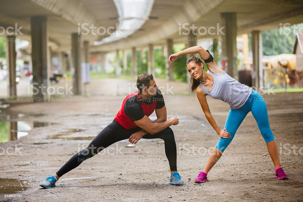 Two people warming up and stretching outdoors. stock photo