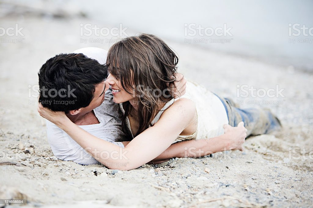 Two people who love each other laying in sand royalty-free stock photo