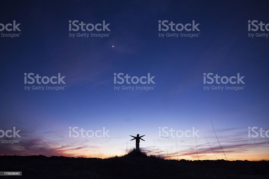 Two people with arms outstretched while standing on beach royalty-free stock photo