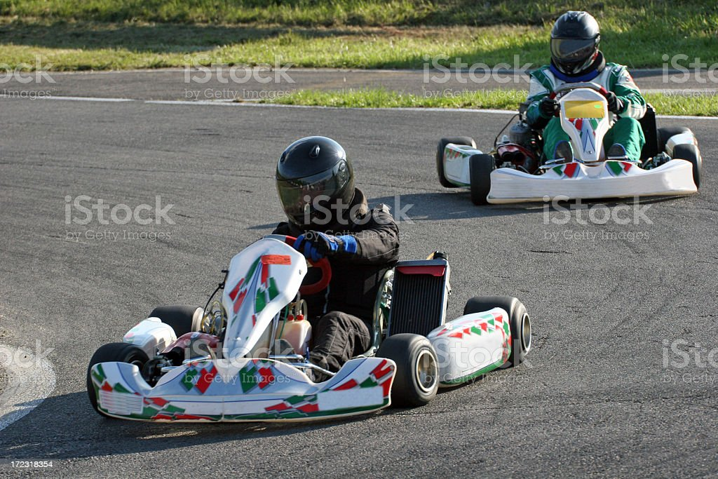 Two people with helmets racing go-carts around a track stock photo