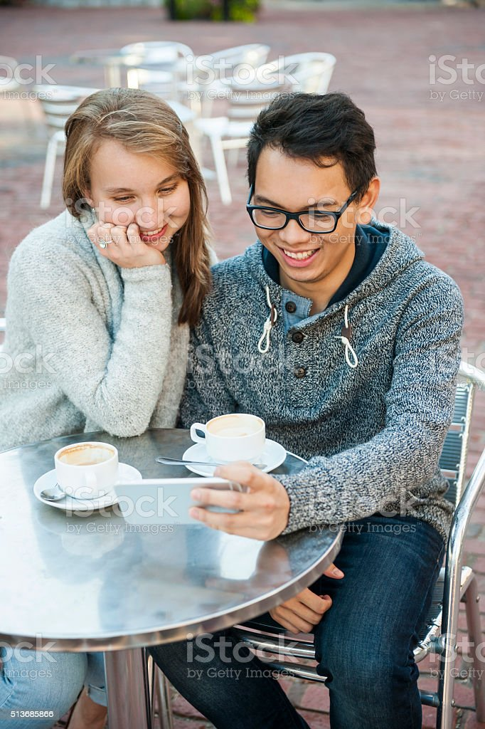 Two people with smartphone in cafe stock photo