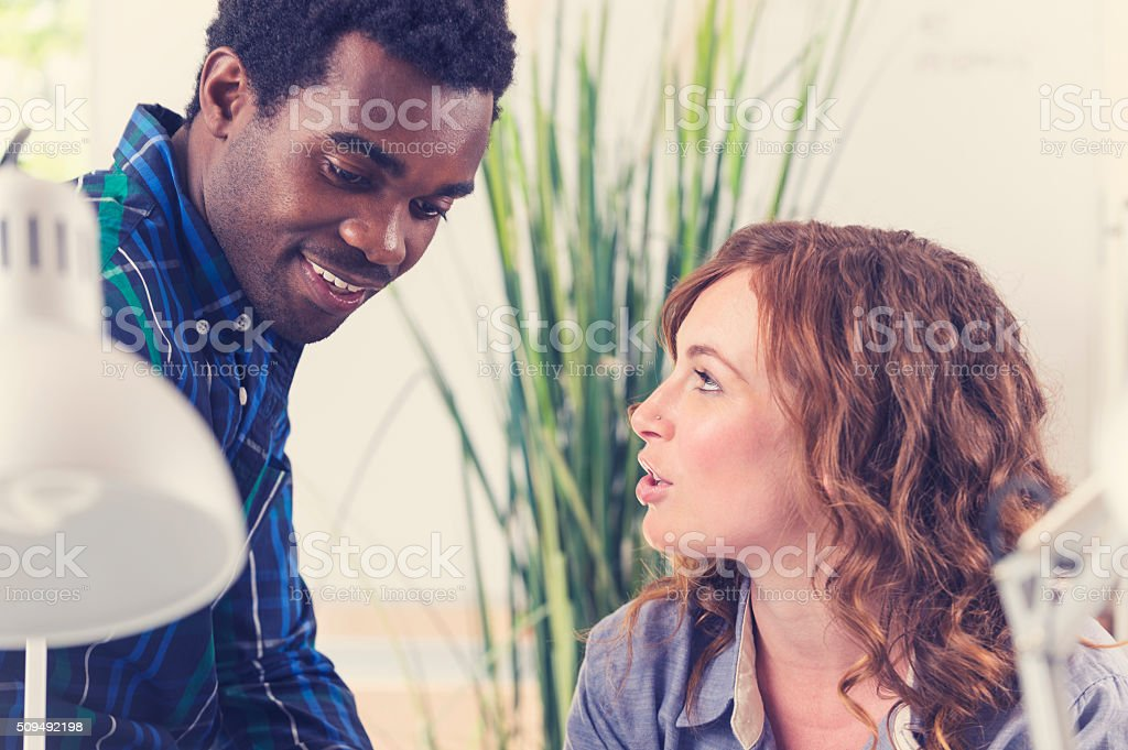 Two people working together with laptop computer. stock photo