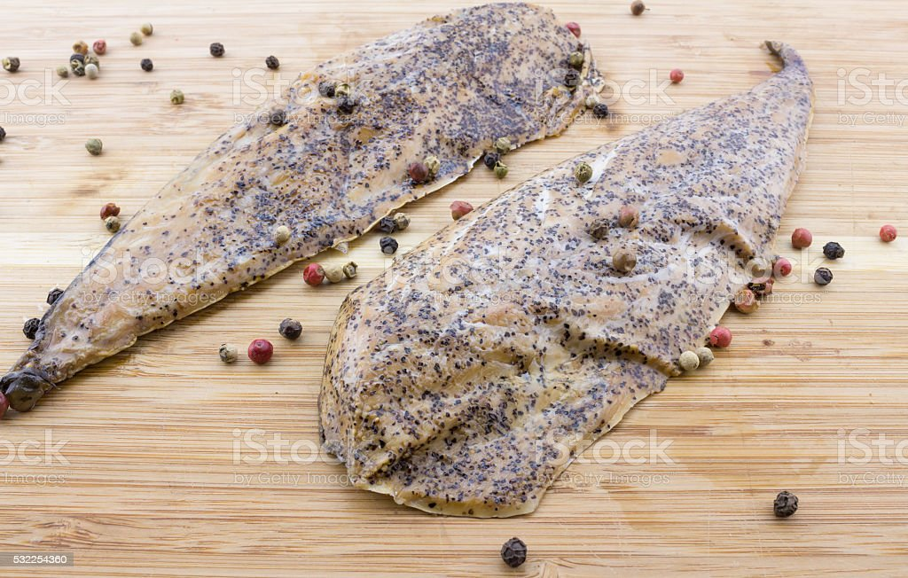 Two peppered, mustard encrusted smoked mackerel on wood cutting stock photo