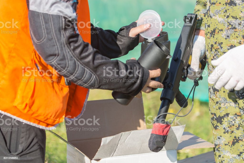 Two persons loading paintball gun with balls outdoors. stock photo